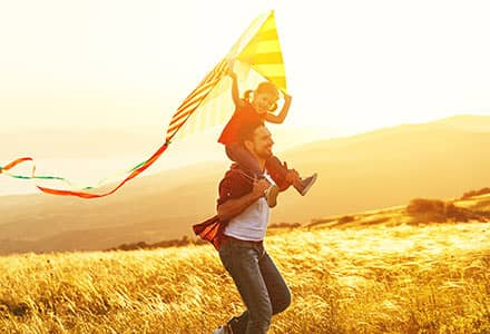 Father holding son on shoulders with a kite