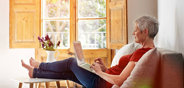 Woman with feet up looking at laptop