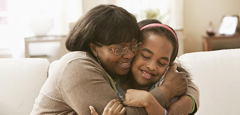 a smiling grandmother hugs her granddaughter in the living room life insurance for children