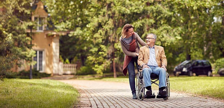 A woman goes for a walk with her disabled father discussing disability insurance