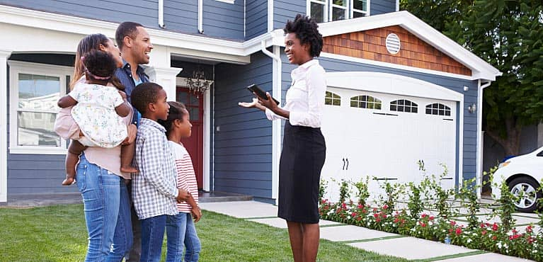 Family standing with real estate agent on the lawn in front of a house for sale: mortgage protection