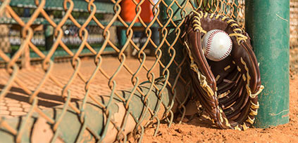 baseball equipment laying against the fence