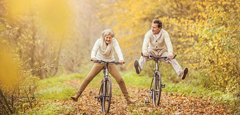 mature couple riding bikes in the fall single premium immediate annuity