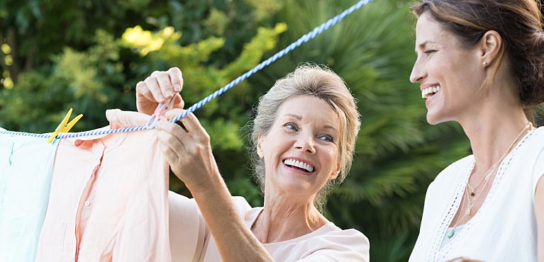 mature mother hanging clothes outside with her daughter benefits of whole life insurance