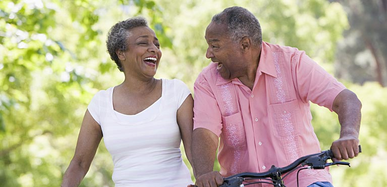 older couple laughing as they ride bikes down a path whole life insurance
