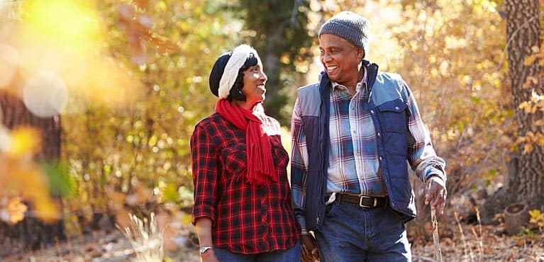retired couple walking through the woods in the fall: immediate annuity