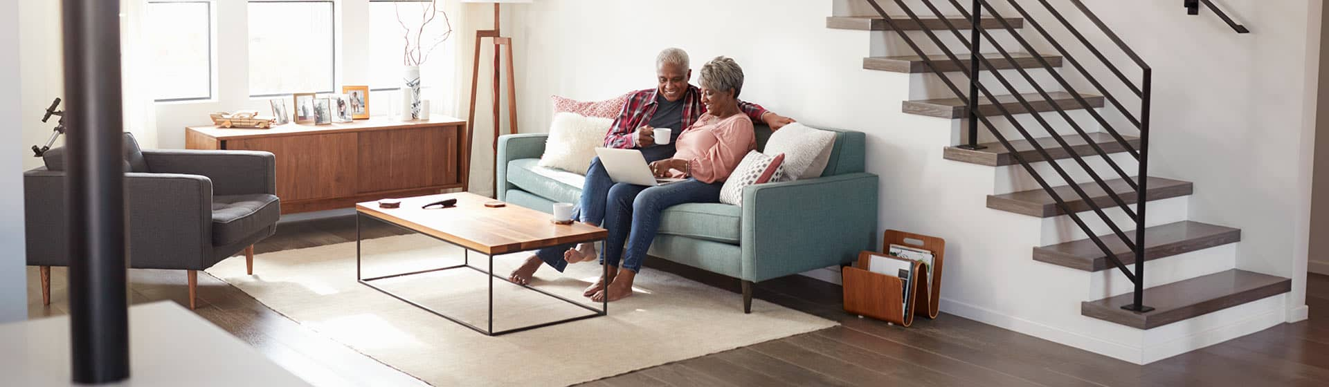 Elderly Couple on the couch using their laptop to check retirement savings numbers