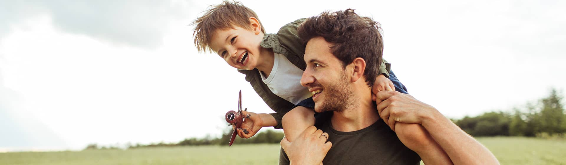 father son playing airplane in a field thinking about financial goals