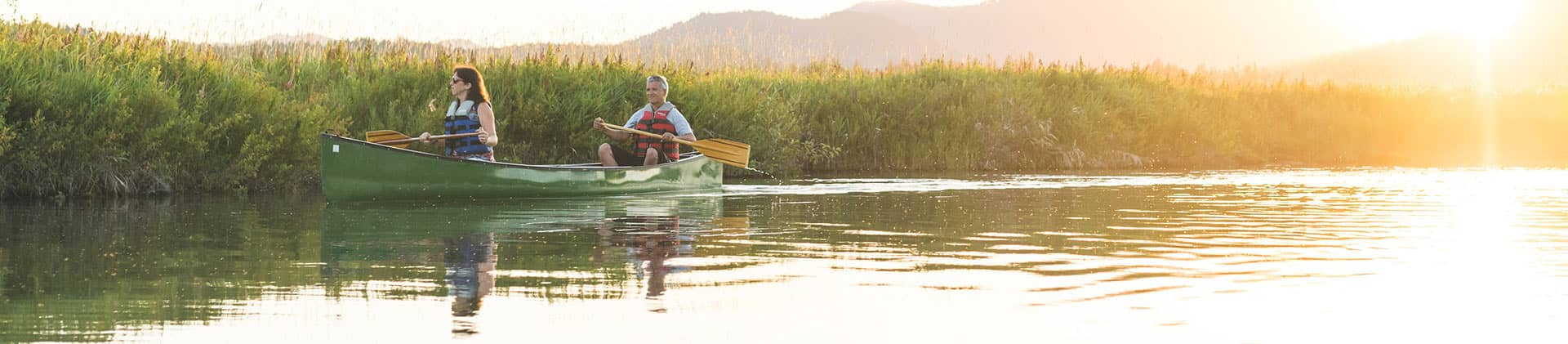 woman and man couple canoeing on lake in mountains talking about new momentum flexible premium deferred annuity and annuities