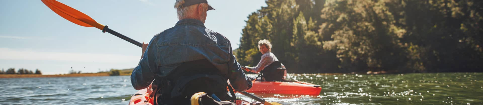 Retired couple kayaking down the river