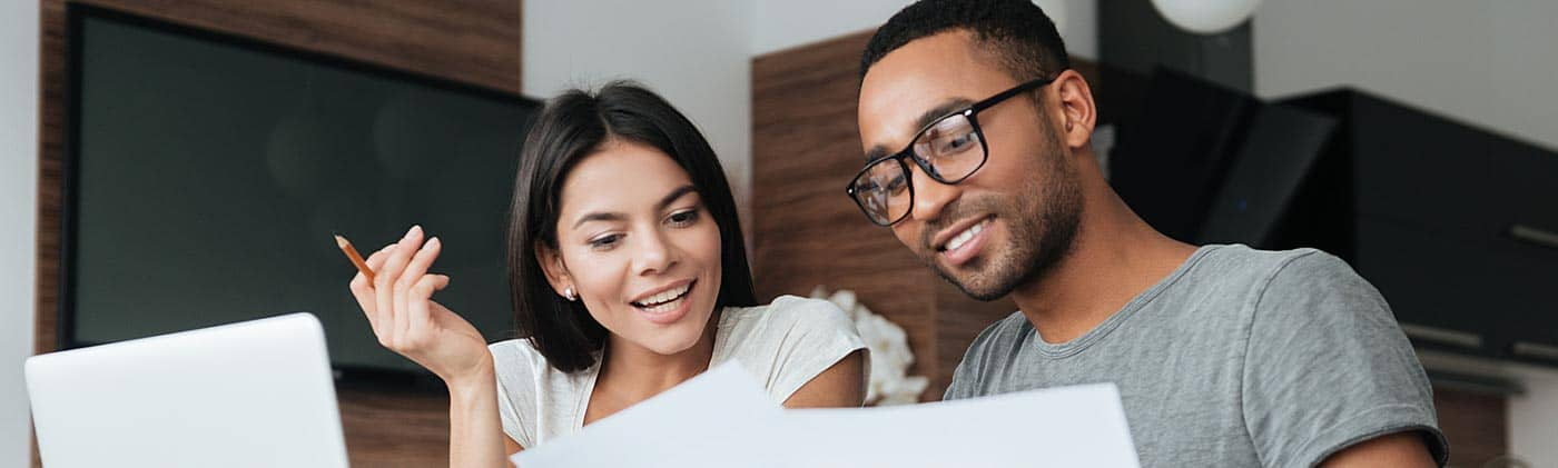 young couple reviews financial documents at home and enjoys the benefits of compounding interest
