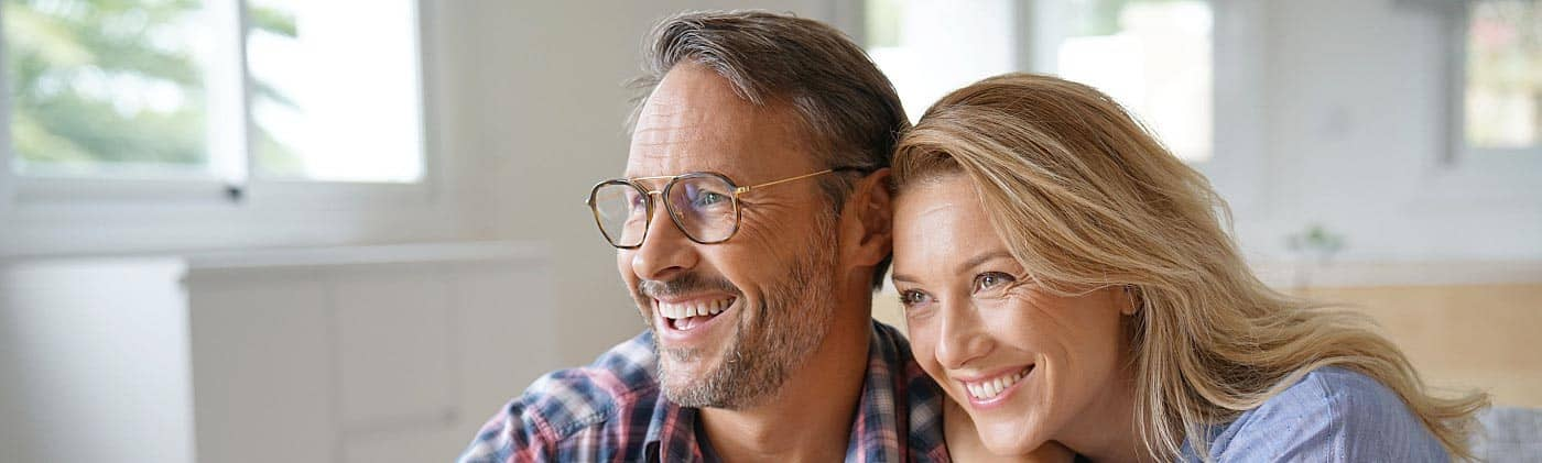 happy 50-something couple relaxes at home and asks each other: how much do I need to retire at 55?