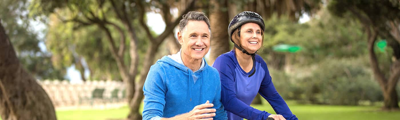 A elder couple riding bikes after researching universal life insurance-
