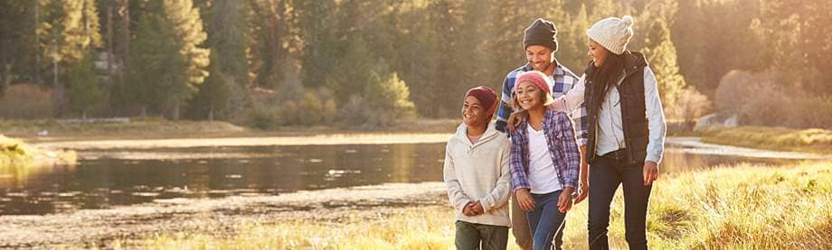 A family of four discusses the advantages of life insurance while on a sunny hike