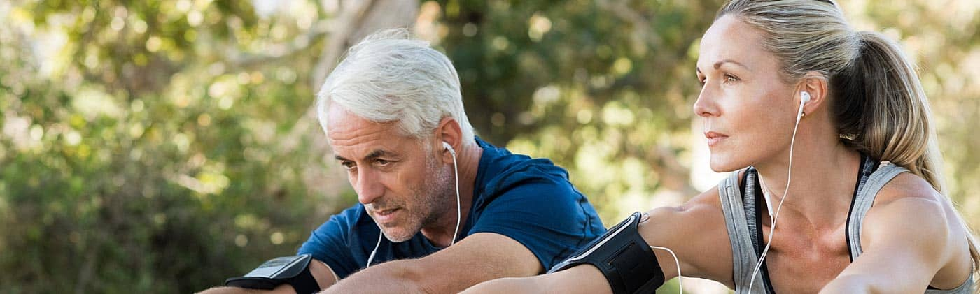 fit senior couple listens to music with earbuds and stretches before a run as part of staying healthy