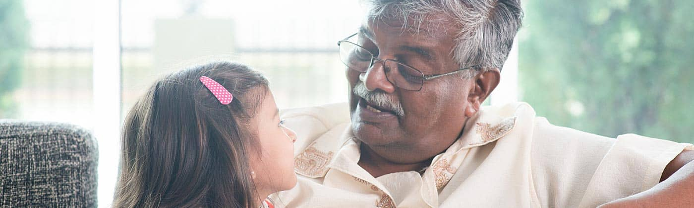 A grandfather eats cake with his young granddaughter at home: multiple life insurance policies
