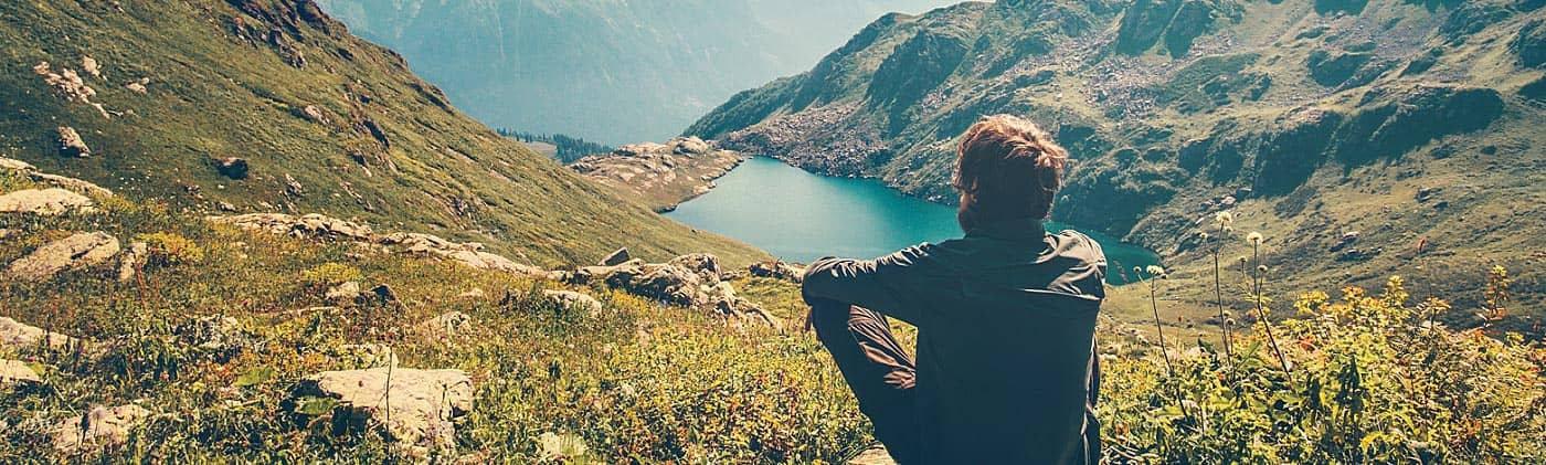 man on hike sits and looks at a beautiful mountain lake as he thinks about personal insurance plans