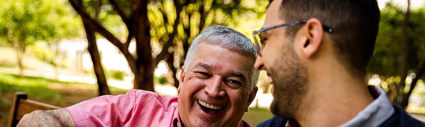 a mature father and his middle aged son laugh together in a park fixed indexed annuity