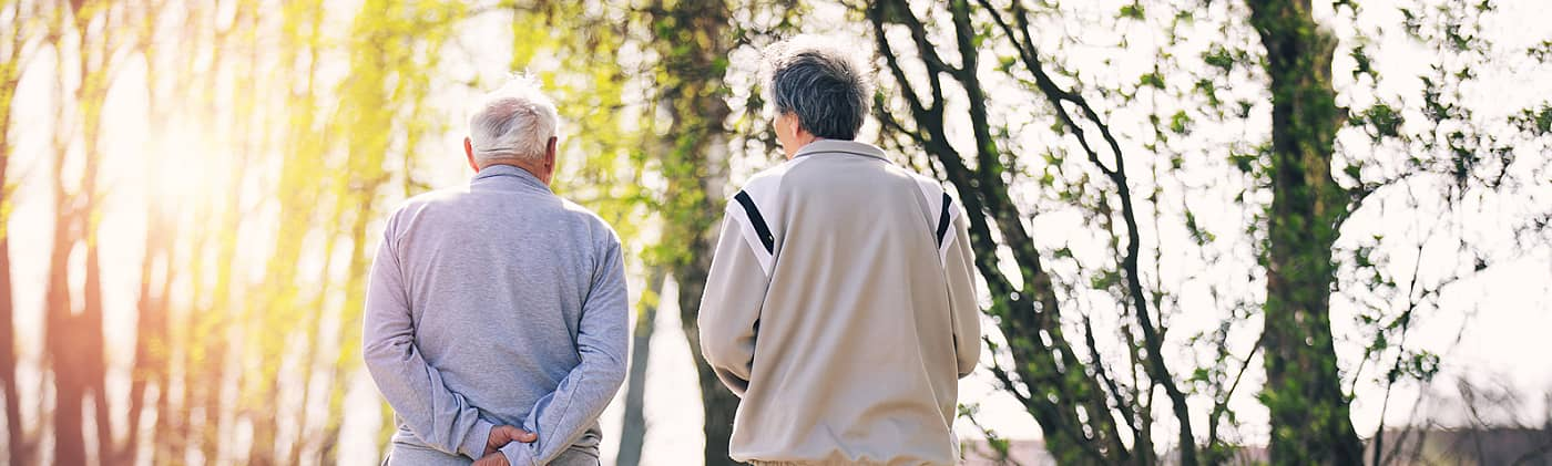 elderly father walks with his adult son down a path at sunset as they discuss estate executor duties