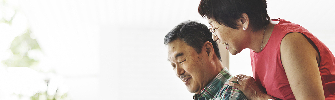 smiling retired couple researches different annuity payment options at home on their laptop