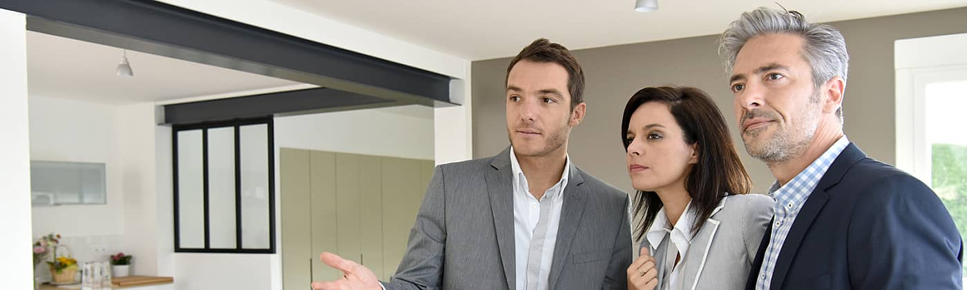 Middle aged couple speaks to real estate age about selling versus renting
