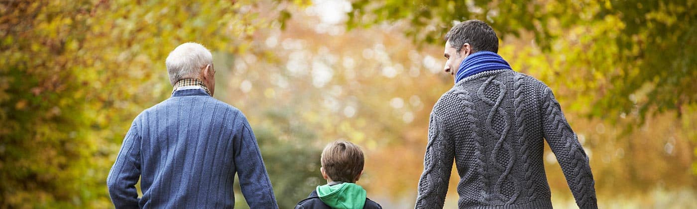grandfather, father and son walk down a path in the fall as adults discuss term life insurance