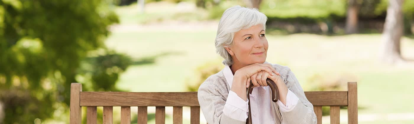 A old woman sitting on a park bench smiling after retiring single