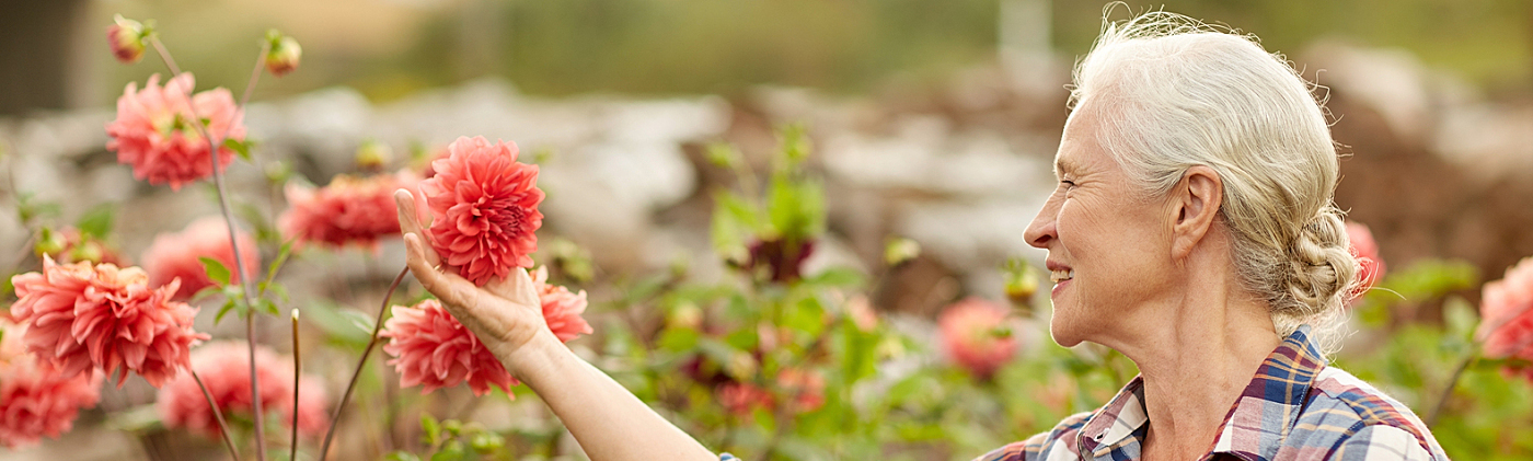 retired woman holds flower bloom in her garden and thinks about options for cash value life insurance