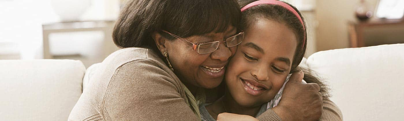 A smiling grandmother hugs her granddaughter in the living room: life insurance for children
