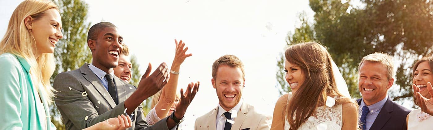 friends throw confetti at bride and groom and counsel them later about when should you get life insurance