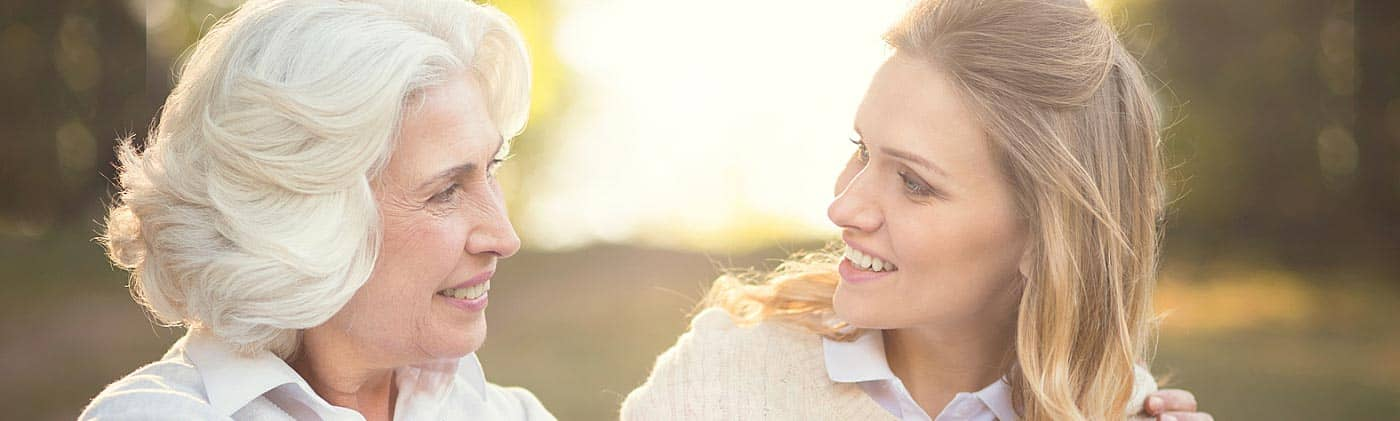 adult daughter talks with her aging mother outside on a sunny day about family financial planning