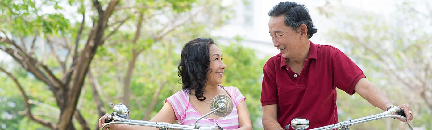 Asian couple riding bikes and discussing 401(k) loan vs. hardship withdrawal