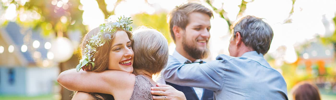 Bride and groom hugging family after successfully figuring out how to save for a wedding