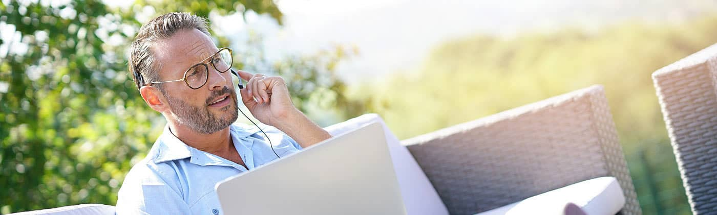 Businessman on the phone while working on his computer outside looking up 401(k) fees