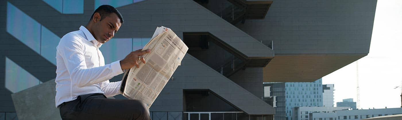 businessman sits outside office and checks performance of mutual funds vs. stocks in newspaper