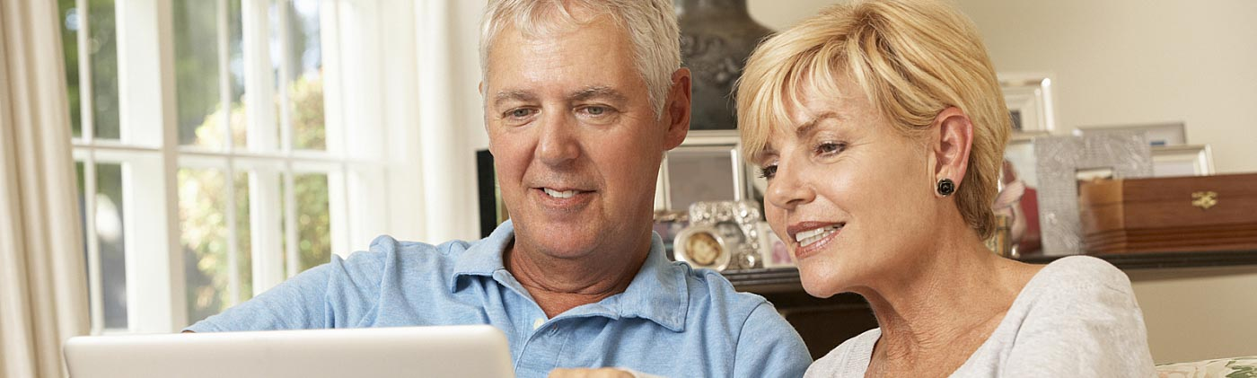 couple begins transition to retirement by reviewing their retirement plan together on laptop at home