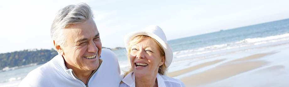 couple laughs and walks on the beach and discusses the question: how much do I need to retire at 62