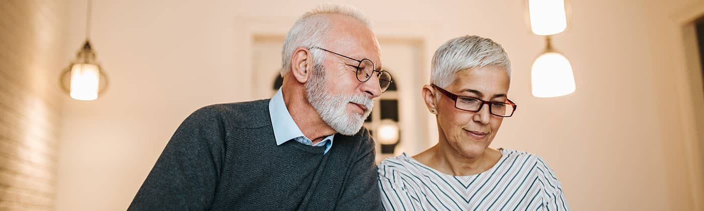retired couple at home researching the question: what does the average funeral cost?