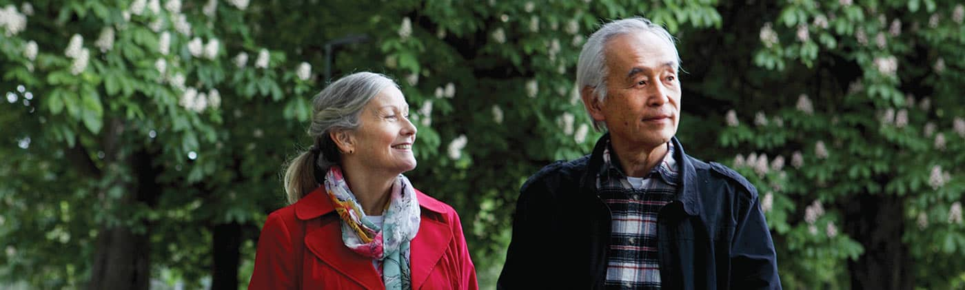 Couple walking through park empty nester consider shaking up your financial plan