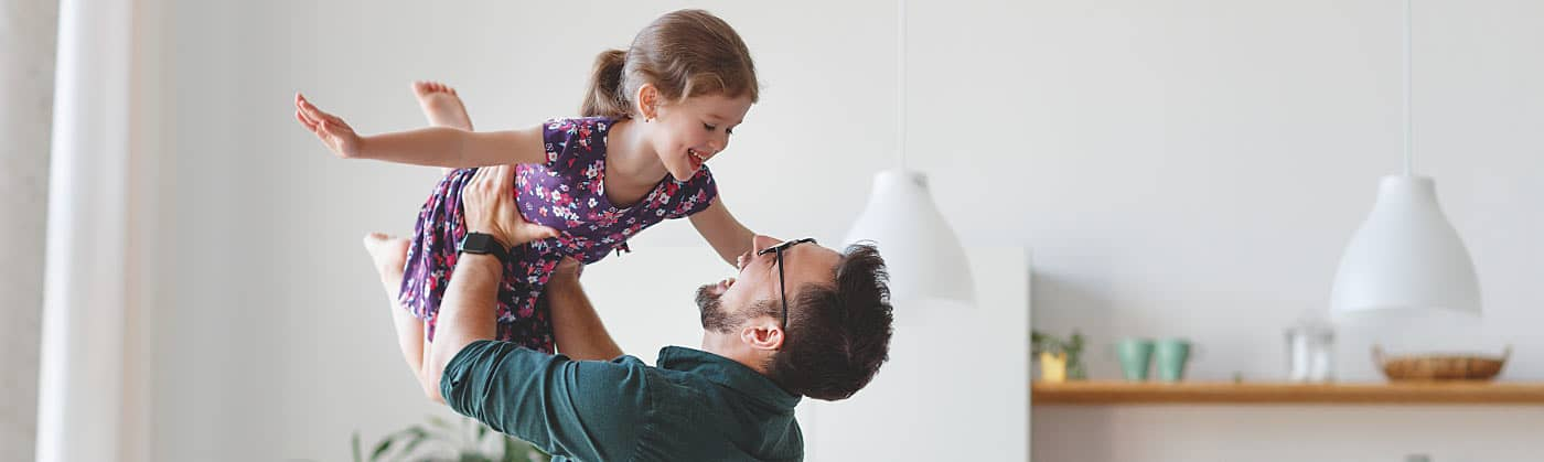 Dad and daughter having fun after dad researched how life insurance works
