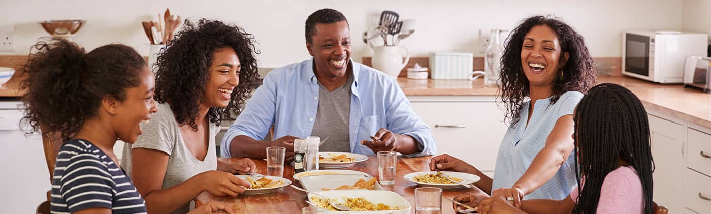 family of five eats dinner together as parents think about how to choose a life insurance beneficiary