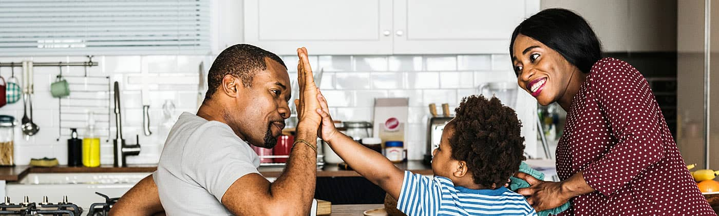 Father high-fives his son while mother watches after parents discuss their annuity options.