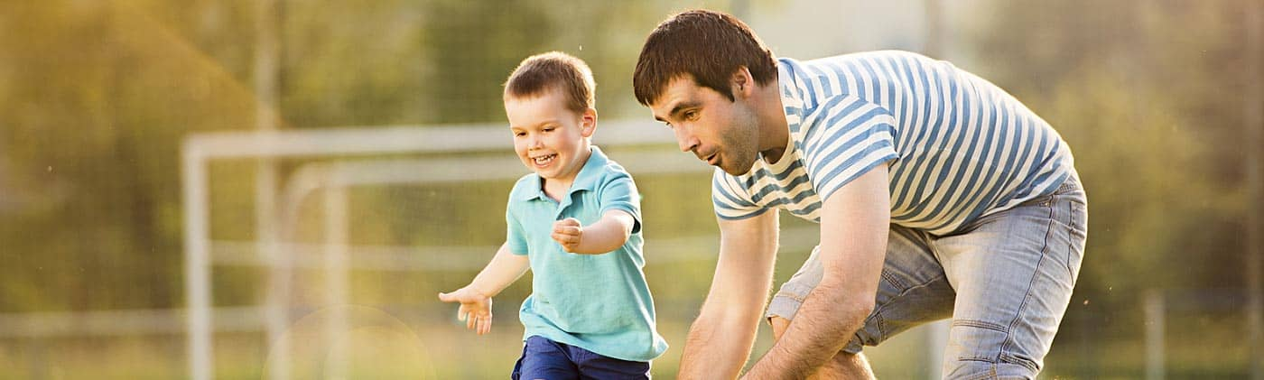 young father with dividend-paying whole life insurance policy plays soccer with his young son