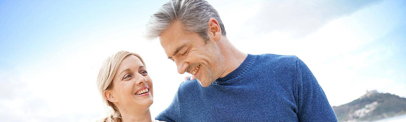 happy middle-aged couple walks along the beach and discusses buying single-premium life insurance
