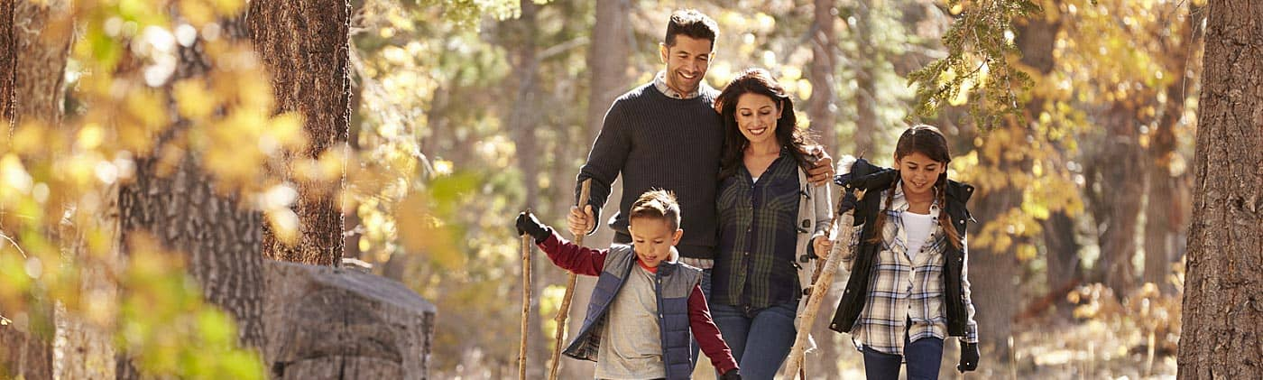 parents think about 10-year term life insurance as they walk in the woods with their daughter and son