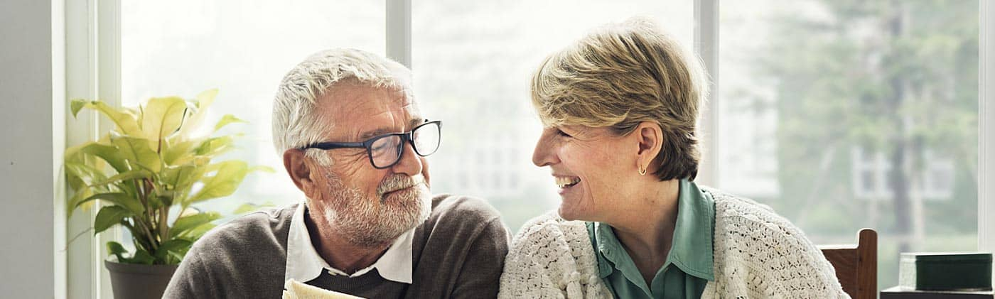 happy older couple eating a meal together: when to start saving for retirement