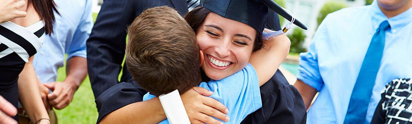 kid brother hugs older sister at college graduation as family is successful in how to save for college