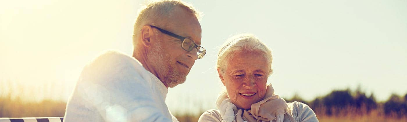 happy retired couple uses a tablet computer on the beach to research when should you get life insurance