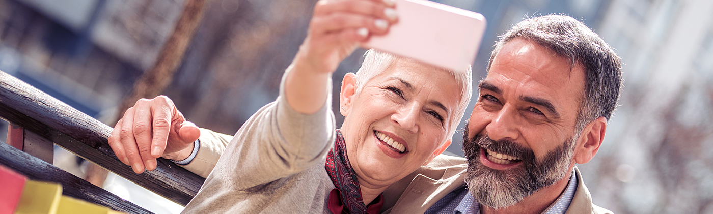 happy senior couple takes a selfie and imagines retiring together due to solid retirement planning