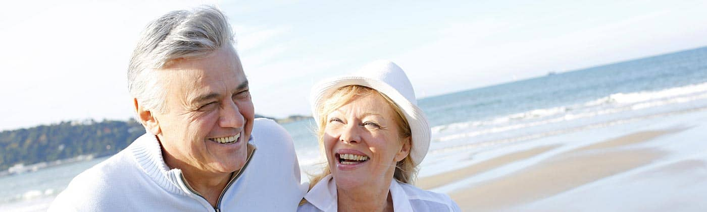 happy senior couple walks along the beach and realizes how important it is to save for retirement